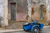 A blue motorcycle with sidecar is parked next to crumbling building.