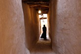 A woman in silhouette down a narrow corridor.