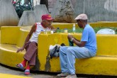 Two friends have a conversation as they sit on a bright, yellow bench.