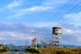 A water tower sits on the side of a road beneath a marble blue sky.