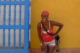 A woman in a red shirt and bandana smiles for the camera as she stands before a vibrant yellow wall.